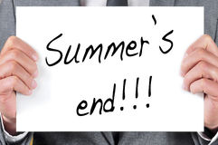 Summers end. A man in suit holding a blackboard with the sentence summers end written in it Stock Images