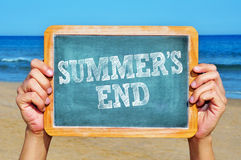 Summers end. Someone holding a blackboard with the sentence summers end written in it on the beach Royalty Free Stock Photo