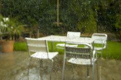 Summers over!. A damp rainy scene showing table and chairs through a window Stock Photography