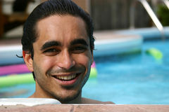 Summers at the poolside. Attractive man at the poolside royalty free stock photography