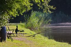 Summertime. Photo of a grassy lakeside with overhanging trees, fishing rods and stool on a sunny morning Stock Image