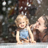Summertime. Happy child and woman in fountain splashes royalty free stock images
