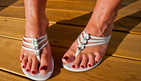 Womans feet in Summertime sandals on new wooden deck. Royalty Free Stock Photo