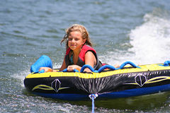 Summertime. Young girl riding the tube on the lake Royalty Free Stock Photography