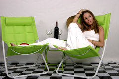 Summertime. Beautiful brunette model on green lounge chair with bottle of wine and glasses next to her Stock Image