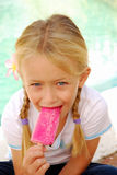 Summertime. Cute little caucasian girl sitting outdoors eating pink sorbet ice-cream in summertime stock photography