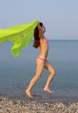 Summertime. Beautiful young woman running along the sea shore light motion blur stock photography