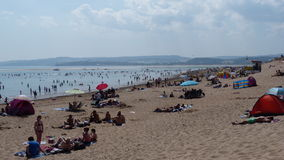 Summertime on a beach in Exmouth South West England. Sunbathers on a beach in Exmouth Devon South West England on a hot July day #Exmouth Stock Photo