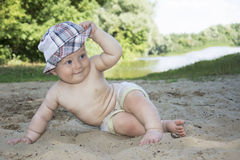 Summertime at the beach near the river sits funny little boy and Stock Image