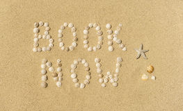 Summertime - book now. The words BOOK NOW written with small snail shells in sand Royalty Free Stock Images