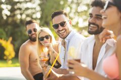 Summertime cocktail party. Group of friends at a poolside summer party, sitting at the edge of a swimming pool, drinking cocktails and beer and having fun royalty free stock image