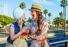 Mother and daughter tourists showing tongues after drinking brig. Summertime at colorful Barcelona. happy stylish mother and daughter tourists on embankment in Stock Images