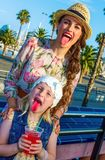 Mother and child travellers showing tongues after drinking. Summertime at colorful Barcelona. smiling stylish mother and child travellers in Barcelona, Spain Stock Image
