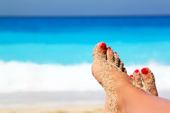 Summertime concept. Crossed legs on the beach as summertime concept stock photography