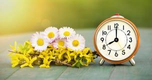Summertime banner - fresh flowers and alarm clock Stock Photos