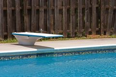 Summertime Cool. Diving board and cool water surrounded by a privacy fence just waiting for summertime fun Royalty Free Stock Images