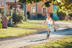 Boy with push scooter Stock Image
