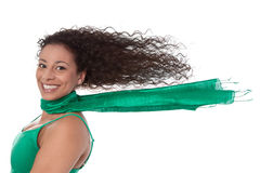 Summertime: Crazy woman in green with blowing hair in wind isolated. Happy young woman - her hair blowing in the wind in a green shirt with long hair royalty free stock images