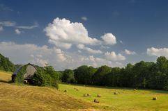 Summertime down on the farm. Barn and haybales down on the farm in Grainger County, Tennessee, USA. Photo by Darrell Young Stock Photos