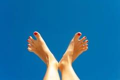 Summertime enjoyment. Woman feet on blue sky background. Royalty Free Stock Photo
