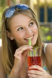 Summertime Fun. A young lady drinking a tall drink ooutside enjoying the summer sunshine Stock Images