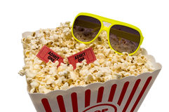 Summertime Fun At The Movies. Isolated on a white background.  Shot of a large tub of delicious popcorn with sunglasses and tickets to the movies Royalty Free Stock Images