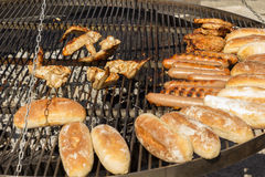 Summertime Grilling. Gourmet sausage and rolls on the grill at a summer backyard barbecue Royalty Free Stock Photography