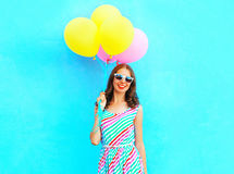 Summertime! happy smiling woman holds in hand an air colorful balloons. Is having fun on a blue background stock image