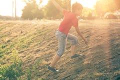 Summertime happyness image of boy climb up slope backlit.  Stock Photos