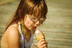 Toddler girl eating ice cream on beach royalty free stock images