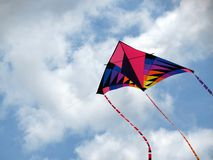 Kite in the Clouds. A brightly coloured kite soars up to the clouds on a summers day stock photos