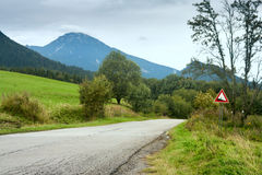 Summertime landscape - view of the road with slope warning sign against the background of mountains Western Carpathians Royalty Free Stock Photos