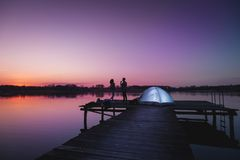 Summertime night camping on the lake. Couple camping on lake docks at dusk, standing next to a tent enjoying beautiful summer night and sky colors right after stock images