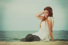 Redhead woman holding sun hat lying on beach stock images
