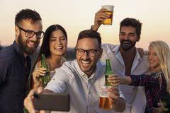Summertime party selfie. Group of friends having fun at an outdoor summertime party, dancing, drinking beer and taking selfies stock photography