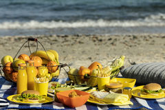 Summertime. A picnic on the beach. Burgers and pitas, vegetables. And fruits. Selective focus Stock Image