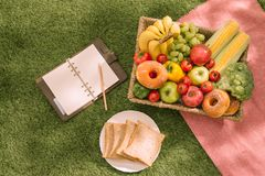 Summertime picnic setting on the grass with open picnic basket, fruit, salad and cherry pie stock photo