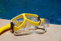 Summertime Pool Fun. Yellow snorkel and mask left at the side of the pool waiting for its' next use during summertime pool fun Stock Photography