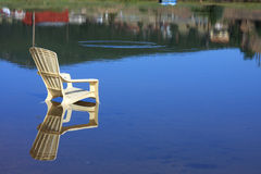 Summertime reflection. Of a chair in a lake with a fish hitting in the background Royalty Free Stock Photography