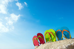 Summertime. Row of colorful flip flops on beach against sunny sky Stock Photo