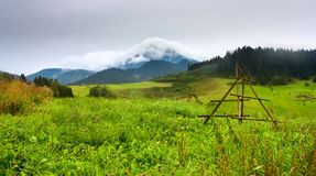 Summertime rural landscape with view at covered with white clouds mount Velky Choc Great Choc in the Slovakia Royalty Free Stock Photo