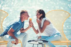 Summertime of woman and man eating ice cream at cafe. Couple in love relax at sea resort. Family and valentines day. Summertime of women and men eating ice cream stock photography