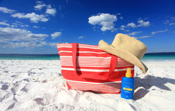 Summertime sun protection sunscreen hat at the beach. Summer sun protection at the beach, each hat and sunscreen on the sand at he beach.  Logos removed Royalty Free Stock Photo