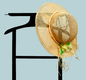 Summertime sunhat on clothes rack, valet over blue. Summertime - fancy sunhat hung on hotel style valet Royalty Free Stock Image