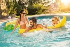 Summertime swimming pool fun. Group of friends at a poolside summer party,  having fun in the swimming pool, splashing water and fighting over a floating royalty free stock photography