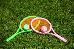 Summertime tennis game. On a green lawn with striped balls Royalty Free Stock Photography