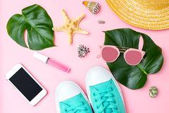 Summertime and travel feminine accessories on pink background. Flat lay royalty free stock image