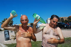 Summertime Two men bathe with water to find the cooler to intense heat Royalty Free Stock Images