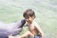 Vacation Lifestyle -Happy Boy hugging a dolphin. Summertime, Vacation Lifestyle -Happy Boy hugging and kissing a dolphin stock photos
