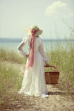 Summertime woman at the beach with picnic basket Stock Images